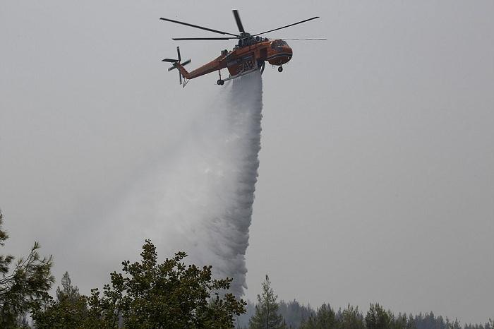 Helikopter menjatuhkan air di hutan yang terbakar